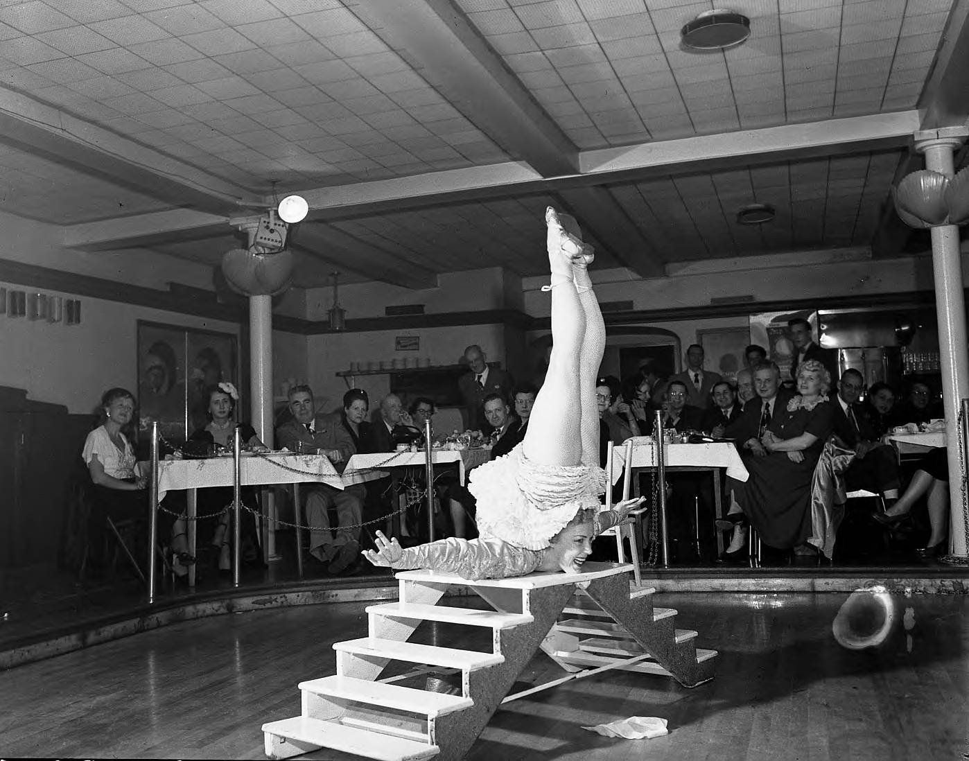 DescriptionA woman acrobat provided part of the evenings entertainment at the Halloween party sponsored by the Tacoma Athletic Commission on October 30, 1950. In this photograph she is balancing on the platform at the top of a small step-platform with her toes pointed straight up at the ceiling. The acrobate is probably Patsy Jean Smith, who studied acrobatics at the Barclay School in Seattle. Mr. Barclay also taught at the Lewis Harter Studios, 945 1/2 Broadway in Tacoma. The Athletic Commission Halloween party was held at the Top of the Ocean.