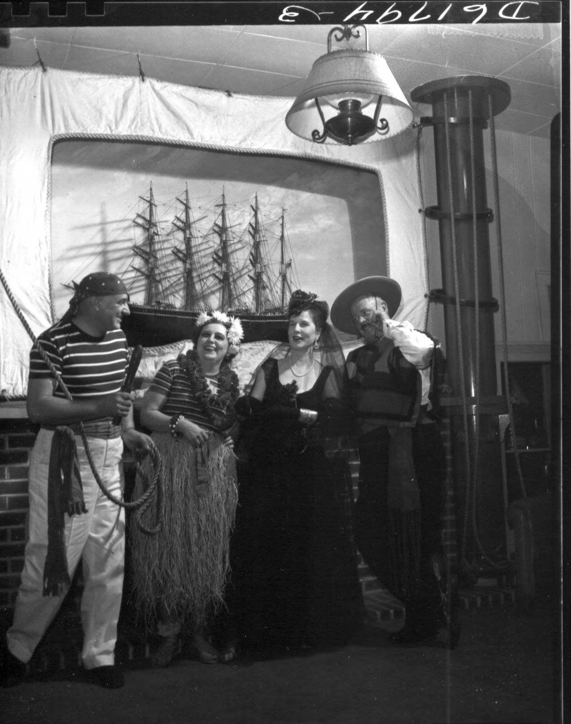 Groups in costumes for Tacoma Yacht Club Halloween Party held on October 27, 1951. Pictured above in front of a ship model are: pirate William Ostruske with Mrs. Ostruske as a hula dancer and Mr. and Mrs. Frank Heffernan as a courtly Spanish couple.