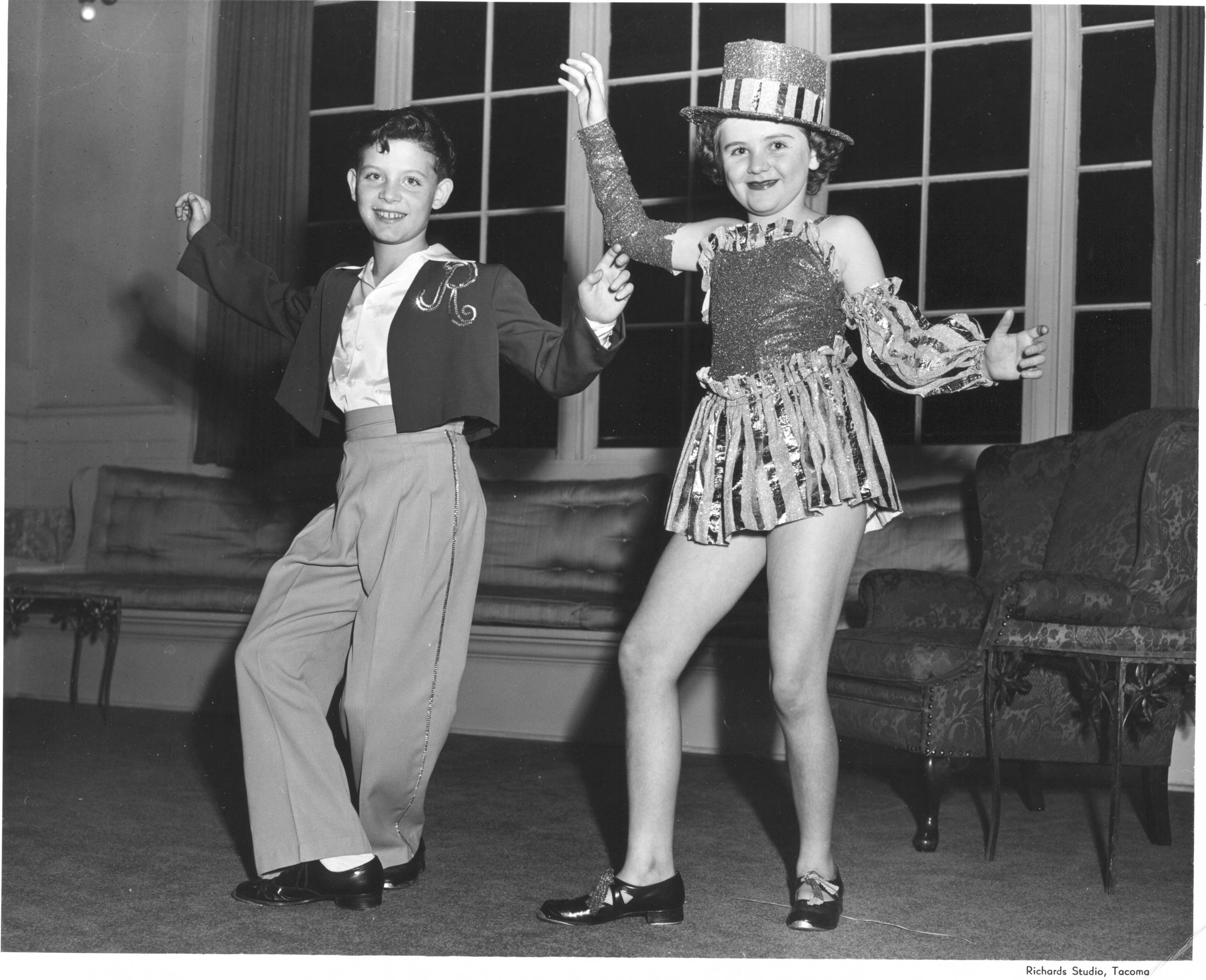 The Tacoma Country and Golf Club had a Halloween party for the children of members in 1951. Two children are shown in mid-step entertaining others; the girl has on a top hat sprinkled with glitter and sparkling short costume while the young boy has on a flamenco style outfit with a large R on his bolero.