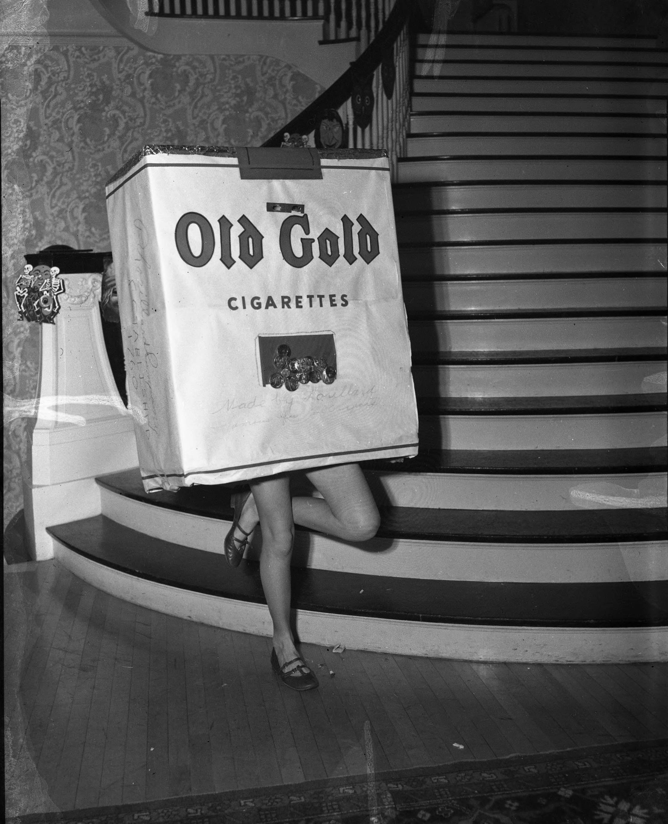 "DescriptionThe Tacoma County and Golf Club held a Halloween party for the children of the members in October of 1951. This unidentifiable young lady, posed at the foot of the club house staircase, came dressed as a dancing cigarette pack. Old Gold's dancing cigarette packs first appeared on television in the late 1940s. By 1951 they were so well known and popular with the public that they were ""TV stars"" even though the dancers inside the boxes were faceless and ""bodyless""."