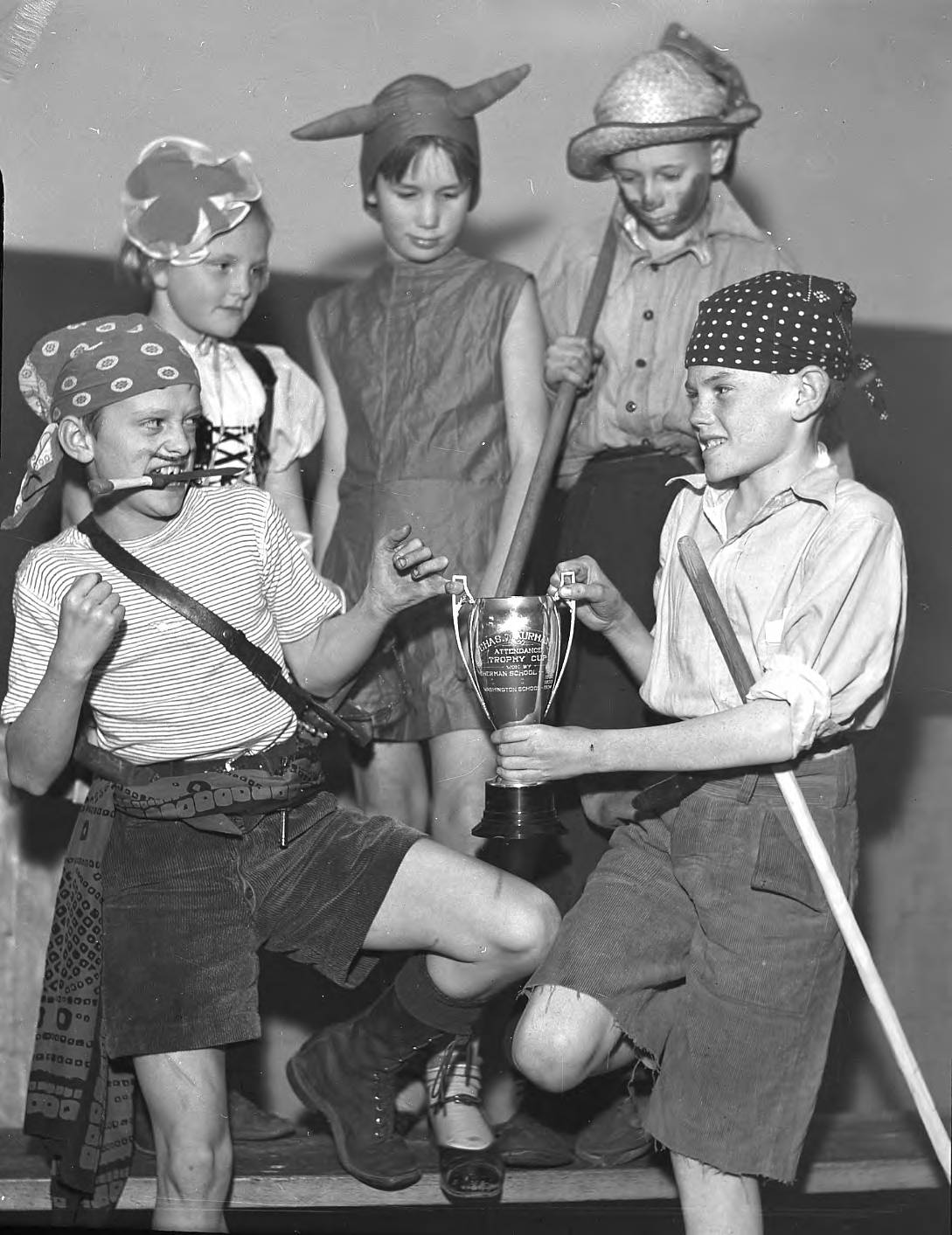 Lyman Burke of Washington School and John Hughes of Jefferson School, togged out as pirates for the Proctor area Halloween costume parade in October of 1935, are ready to do battle for the Attendance Trophy Cup to be awarded to the school having the largest representation in the parade. In back row are Marilyn Wagnild of Jefferson and Betty Jean Woley and Edward Miller of Point Defiance School. Several thousand children and their parents joined in the parade and party sponsored by the 26th & Proctor St. Business Men's Club.(T. Times, 10/31/1935, p. 1)