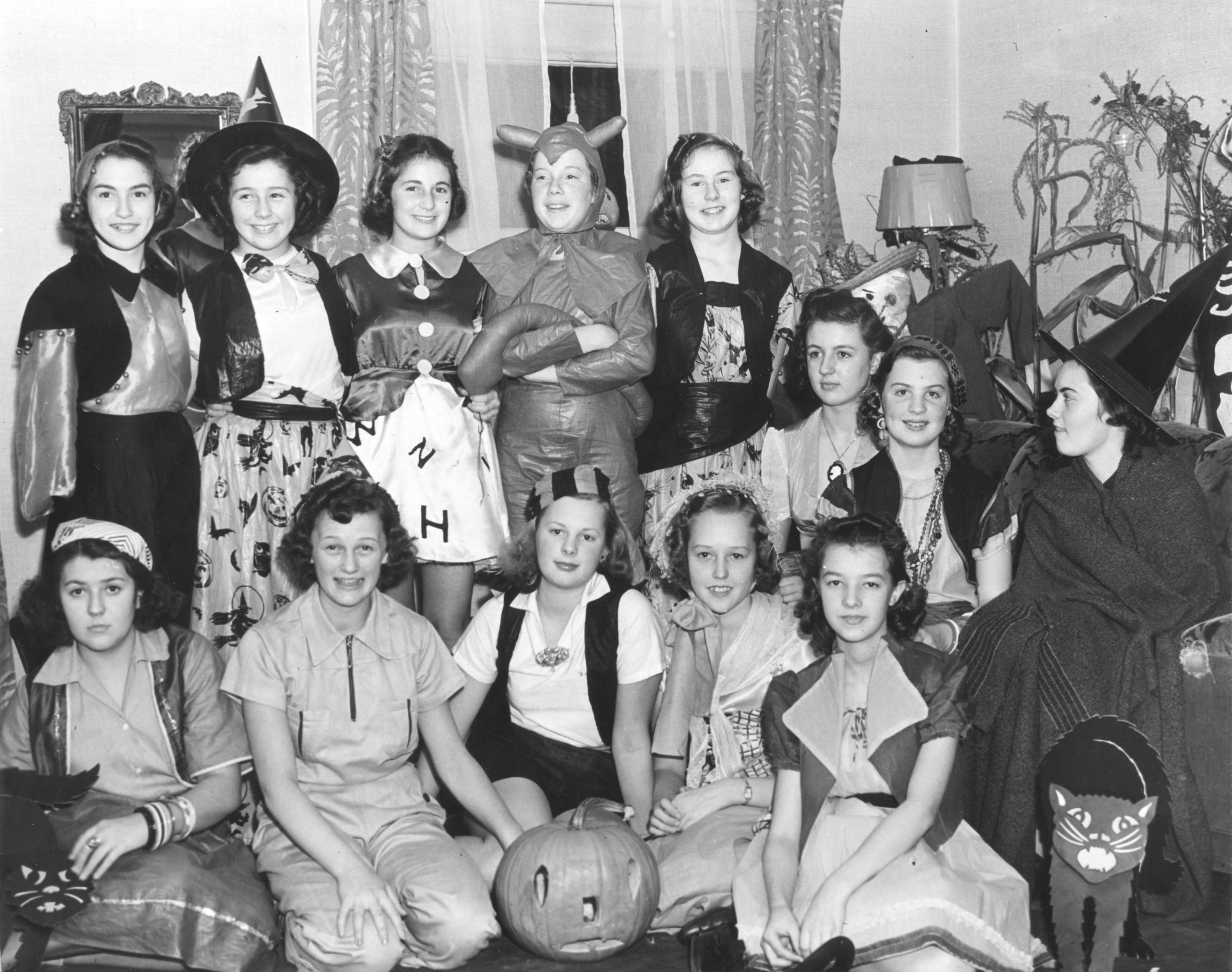 "Miss Peggy Grumbling, in the standing row in ""Devil"" costume, played hostess to several of her friends at this pre-Halloween costume party, held at the home of her parents, Mr. and Mrs. Alfeus Grumbling. Second from left in the standing row is Betty Wilbur. Seated in the front, beginning at second from the left, are Charlotte Dowling, Betty Magnuson and Elnor Deimer. The girls had a buffet dinner and played Halloween games. (T. Times 10/31/1838, pg. 11)"