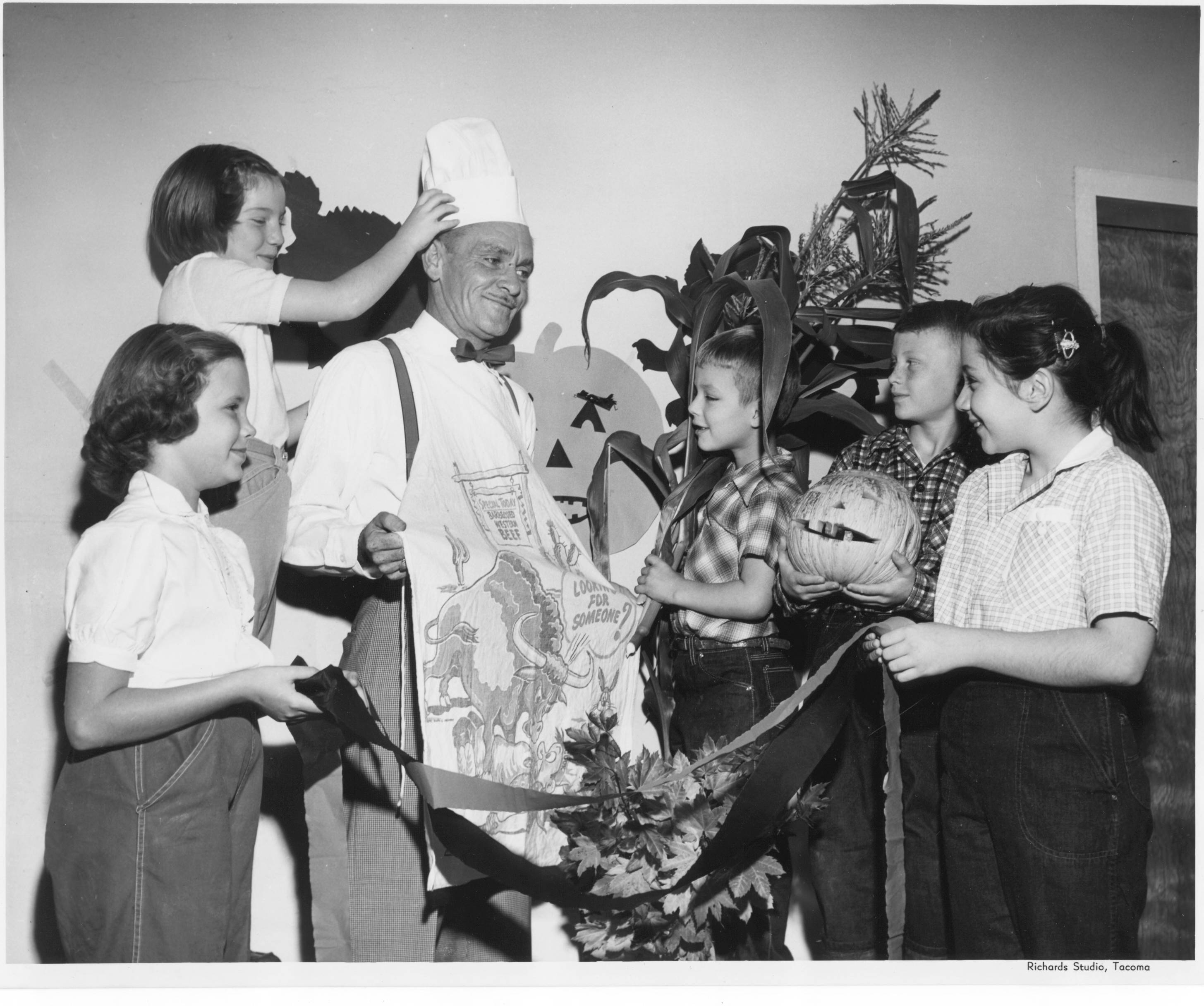 Lowell students and their principal prepare for a howling good time at the '53 Halloween Carnival. The Lowell School Parent-Teacher and Preschool Association sponsored a school carnival on Friday October 23, 1953. Pictured left to right are Sammie Warren, Nancy Conly, principal Clarence Monson, Andy Levesque, Tommy Rowland and Judith Sleep.With his chef's hat and apron, Principal Monson looks as if he'll be manning the hot dog grill. The carnival midway had over 30 booths including fun booths where students could throw darts at balloons or shoes at stuffed animals; food booths with ice cream, hot dogs and pop corn; and craft booths where they could make decorations or put on make-up.