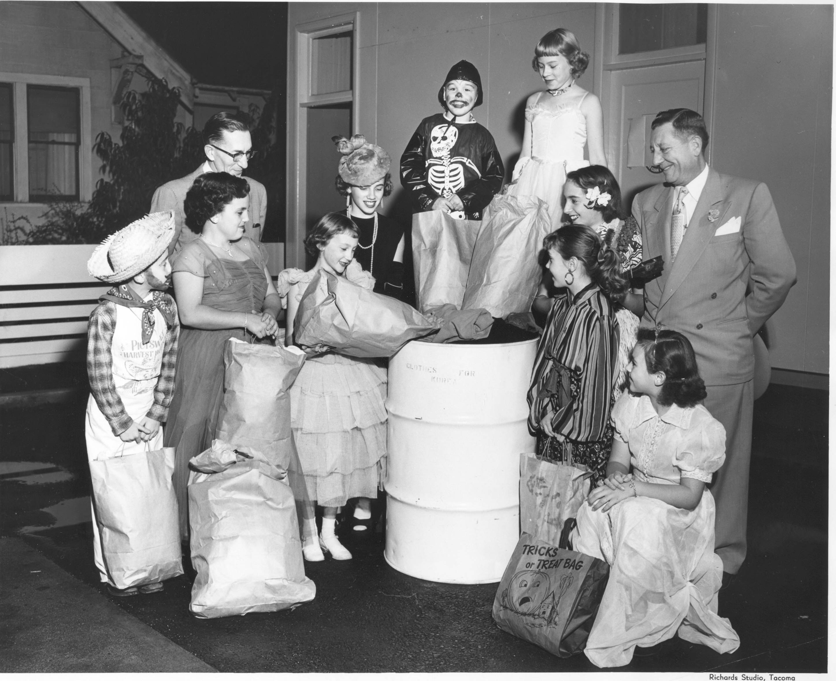 "DescriptionTwo unidentified men watch as nine unidentified Proctor area ""trick-or-treaters"" deposit the clothing that they collected for shipment to Korea, during the Halloween weekend, into marked white barrels. In 1953, the Oil Information Committee of Pierce County was working with the Overseas Relief Committee of the Tacoma Council of Churches to collect warm clothes for the needy in Korea. Items needed included blankets, coats and sensible shoes, children's shoes & clothes, baby layettes and knitting wool and sewing thread. Donations could be taken to service stations and deposited in special white barrels marked ""Clothing for Korea""."
