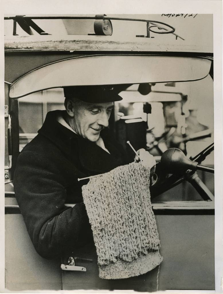 Taxicab driver knitting between fares, London, c. 1940.