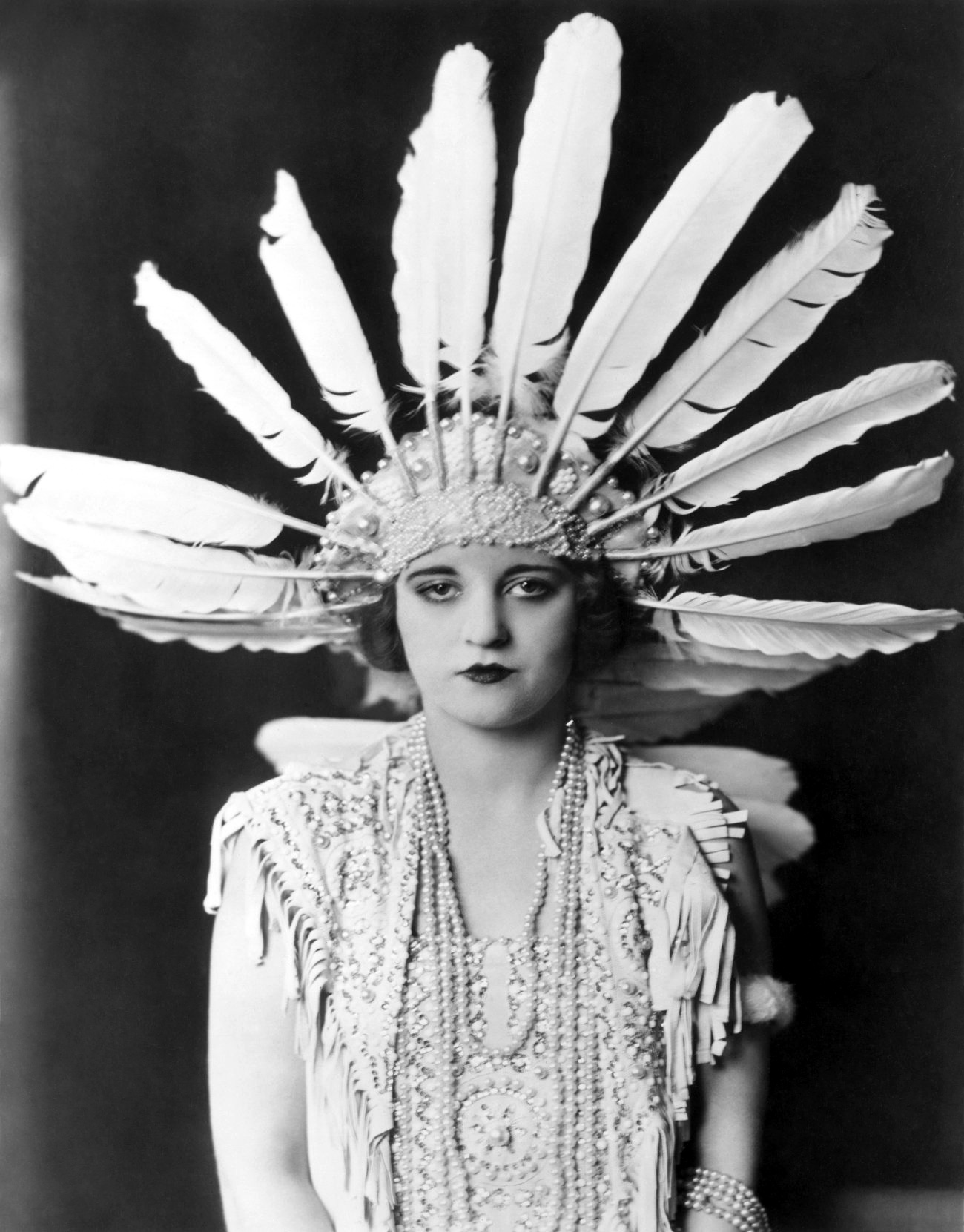 1923: Tallulah Bankhead wearing a large feather headdress and beaded necklaces - The Dancers
