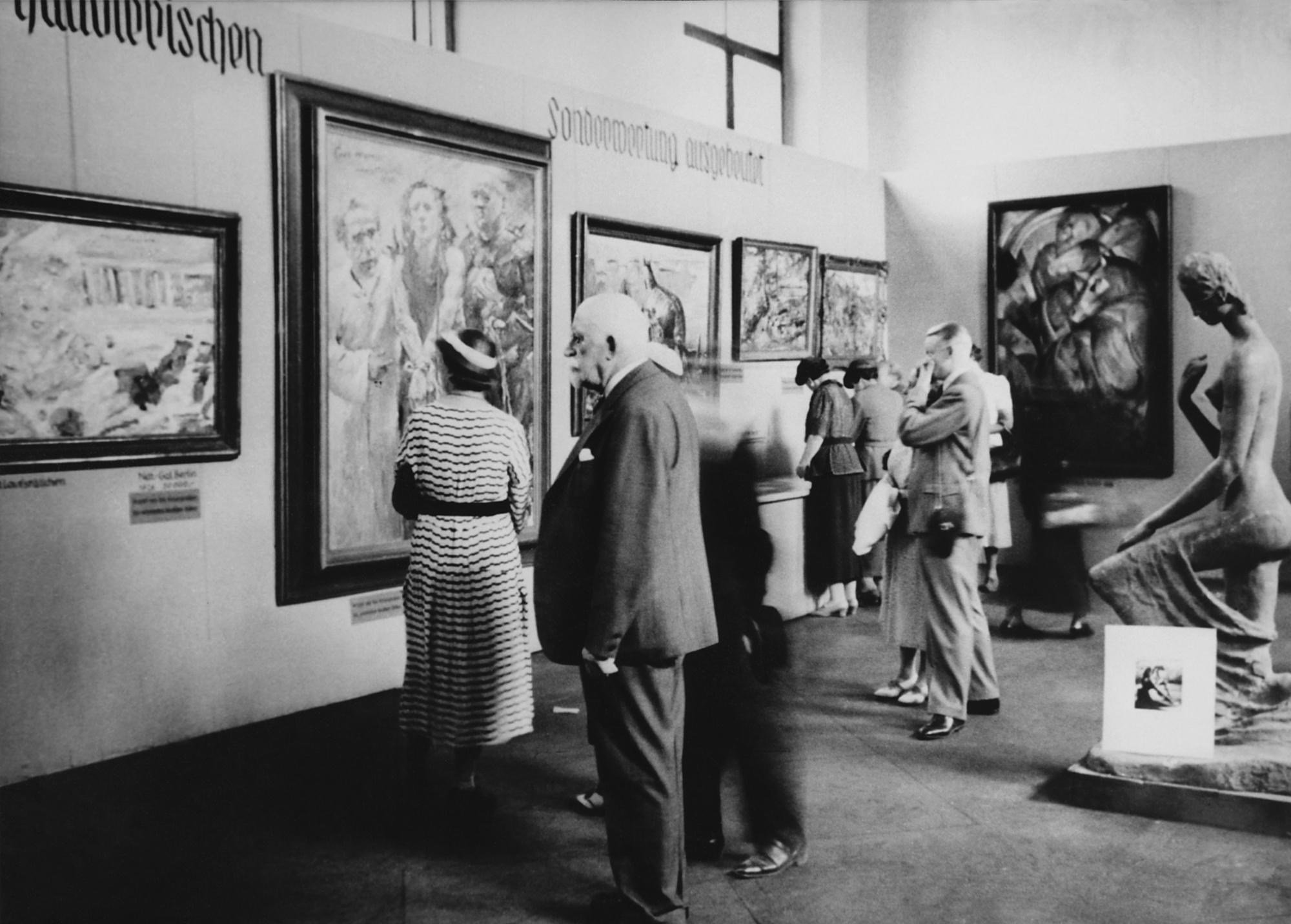 Visitors look at works in the Degenerate Art exhibition in Munich, which opened on July 19, 1937. Pictured are Lovis Corinth's Ecce homo (second from left) and Franz Marc's Tower of the Blue Horses (wall at right), next to Wilhelm Lehmbruck's sculpture Kneeling Woman.