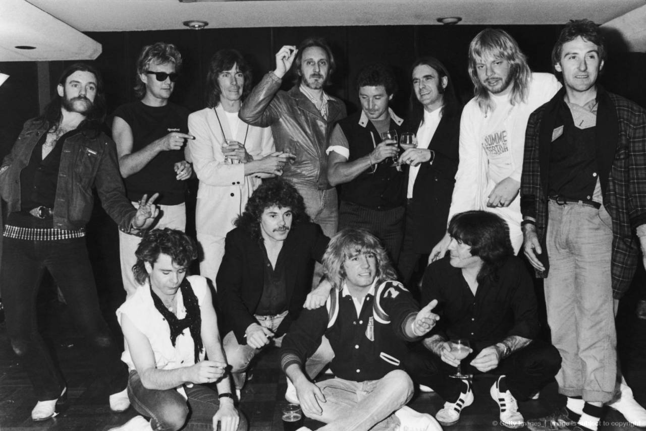 Guests at a farewell party for British rock band Status Quo, 1984.( Back row, left to right:) Lemmy of Motorhead, Roger Taylor of Queen, Andy Bown of Status Quo, John Entwistle (1944 - 2002) of The Who, Kenney Jones, Francis Rossi of Status Quo, Rick Wakeman, Denny Laine. (Front row, left to right:) unknown, Alan Lancaster, Rick Parfitt and Pete Kircher of Status Quo, unknown.