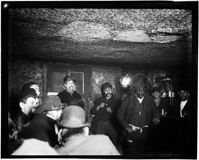 "A Downtown ""Morgue."" DATE:ca. 1890 Men in a crowded in an ""Black and Tan"" dive bar"
