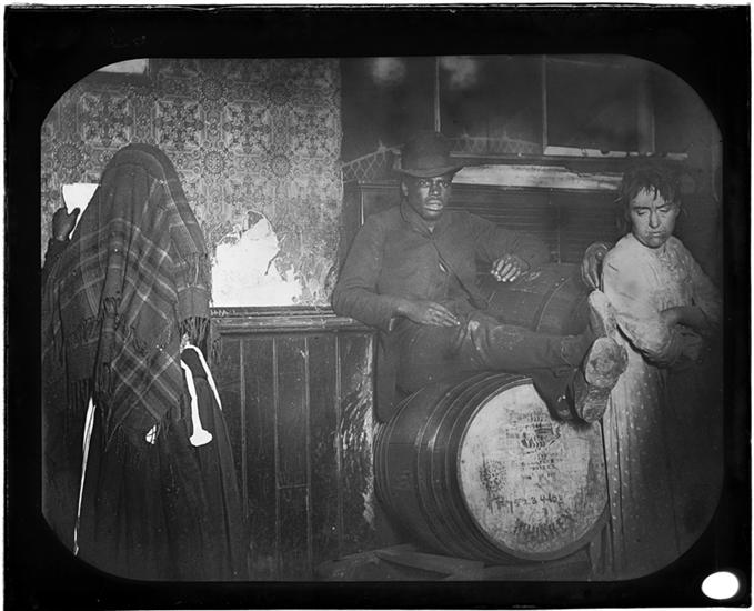 "A Black-and-Tan Dive in ""Africa."" DATE:ca. 1890 An African American man seated on a whiskey keg flanked by two women in a ""Black and Tan"" dive bar on Broome Street near Wooster Street."