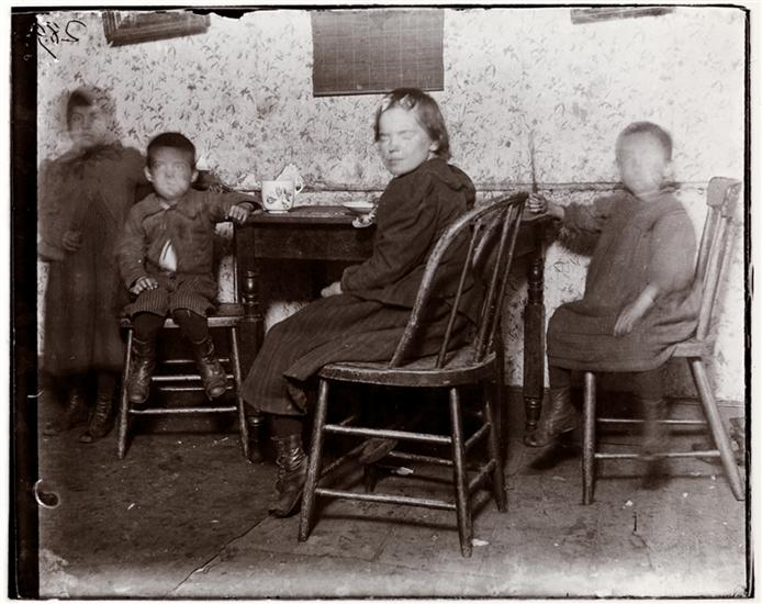 "Children in ""The Ship,"" destroyed by B. of Health in 1897, after the visit of Roosevelt & myself [Jacob A. Riis] there. DATE:1895 Four children at a table, eating, in a tenement building known as ""The Ship"" on Hamilton Street."