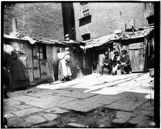It costs a Dallar a Month to sleep in the Sheds. DATE:ca. 1897 A woman holding a child, and men sitting in a rear yard of a Jersey Street tenement.