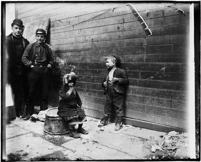 Two Greek children in Gotham Court debating if Santa Claus will get to their alley or not. He did. DATE:ca. 1890