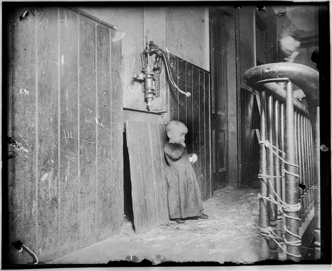 Baby in slum tenement, dark stairs--it's playground. DATE:ca. 1890