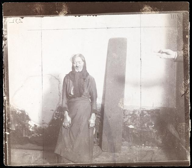 "A ""Scrub"" and her Bed -- the Plank. DATE:ca. 1890 An old woman with the plank she sleeps on at the Eldridge Street Station women's lodging room."