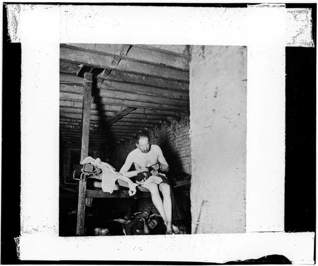 Jacob Riis 1900 New York City Lodger in Pell Street 7 cents lodging house (Happy Jack's Canvas Palace) going to bed. DATE:ca. 1890