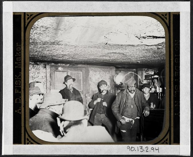 "A Downtown ""Morgue."" DATE:ca. 1890 Men in a crowded in an ""Black and Tan"" dive bar."