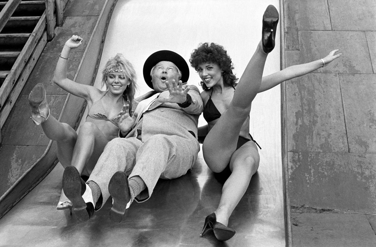 Comedian Benny Hill slides down a slide with two bikini clad women during filming for his latest series (1983).