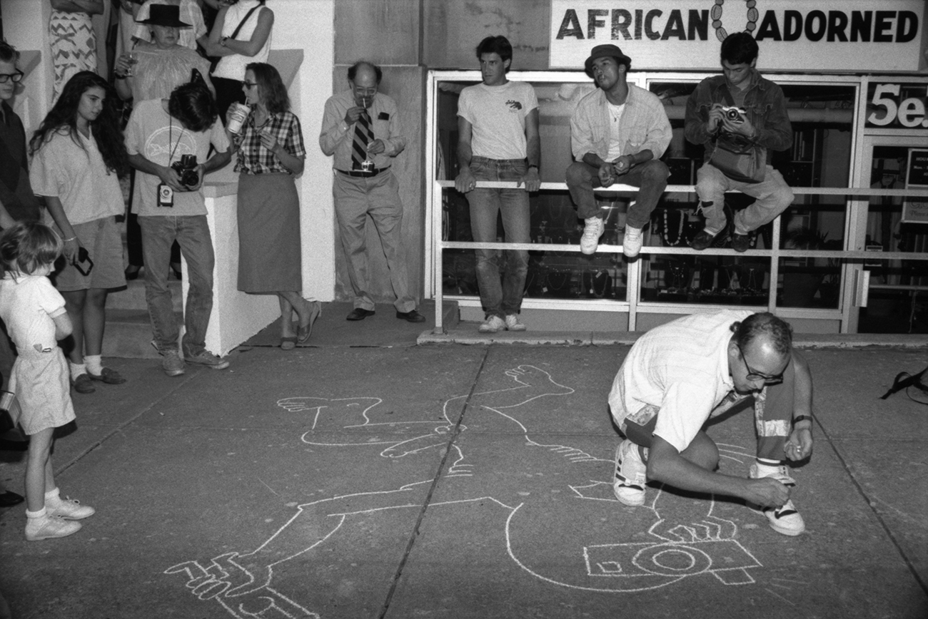 Keith Haring draws on sidewalk in downtown Lawrence. Kansas