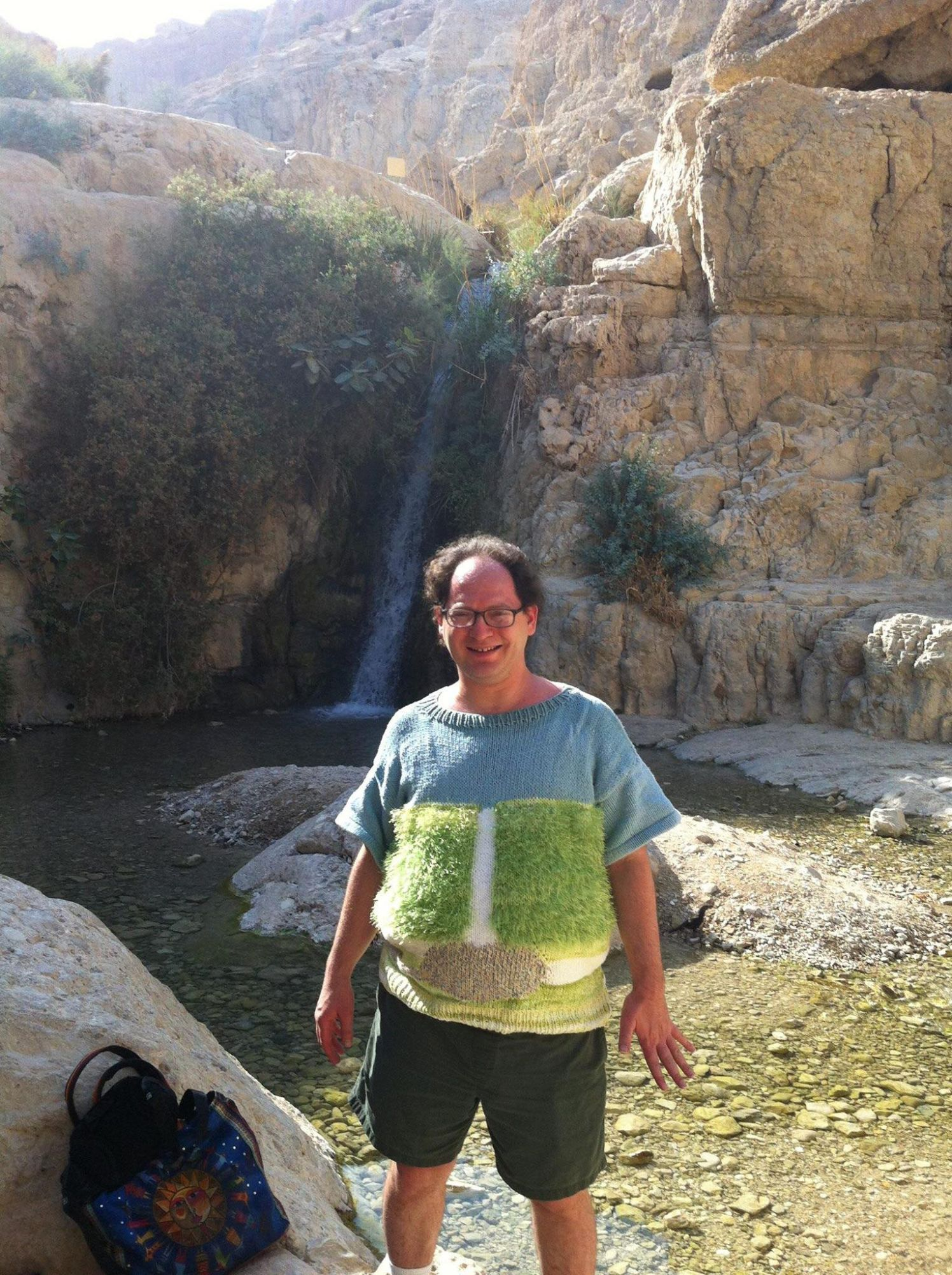 Sam Barsky at Ein Gedi, near the Dead Sea, wearing his sweater depicting the Ein Gedi waterfall