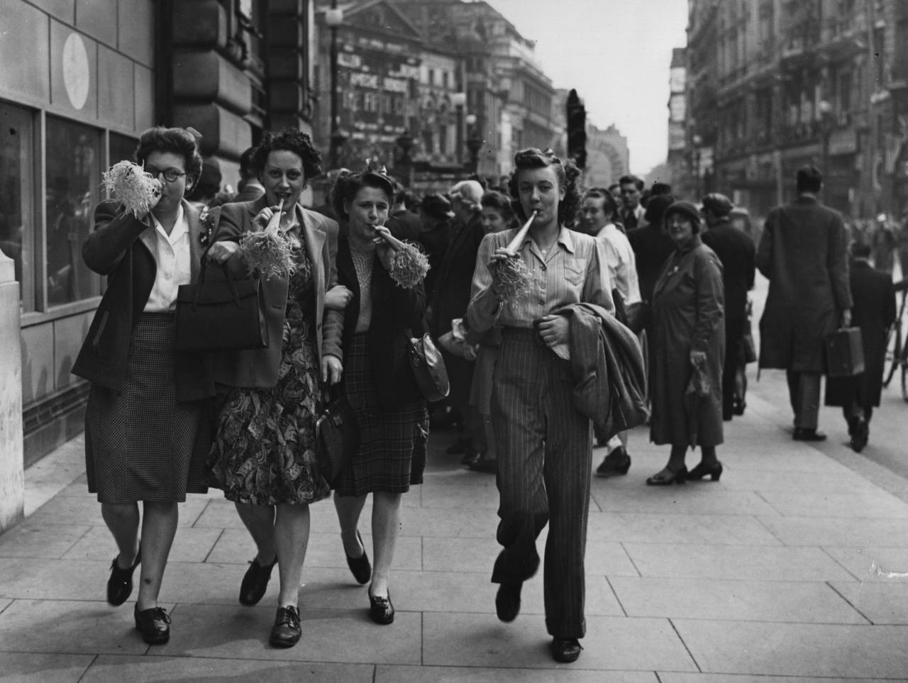 8th May 1945: VE Day revellers blowing party trumpets in Piccadilly, London. (Photo by Topical Press Agency/Getty Images)
