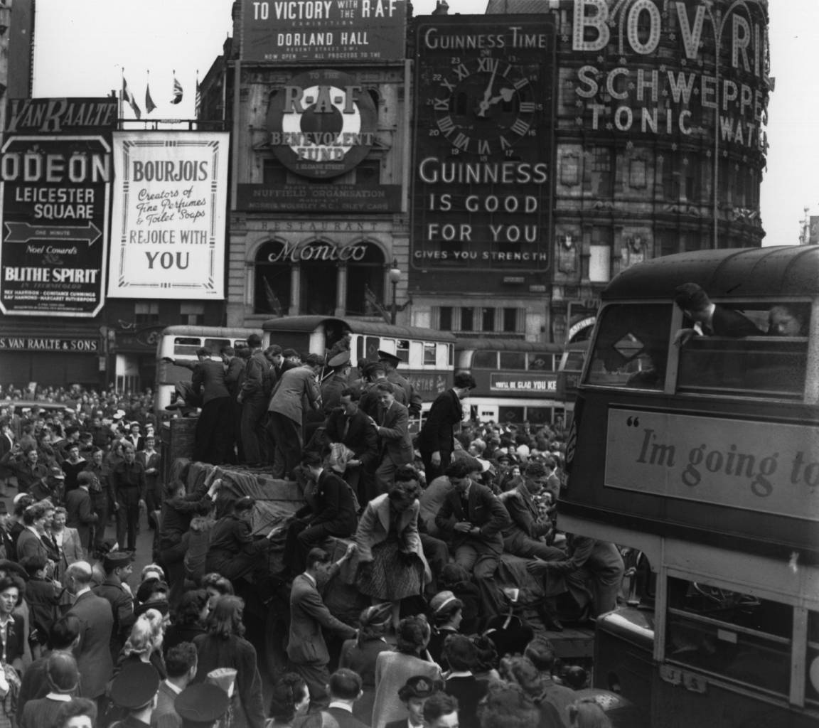 8th May 1945: Crowds clamber on trucks and buses during the VE Day celebrations in Piccadilly Circus. (Photo by Keystone/Getty Images)