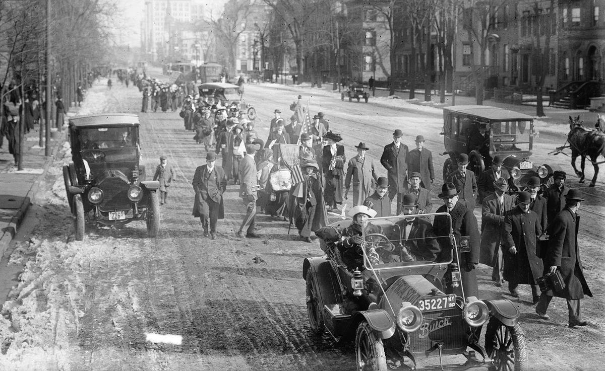 "The hike lead by ""General"" Rosalie Jones from New York to Washington, District of Columbia, for the March 3, 1913 Suffrage parade. Photo taken in Newark, New Jersey on Broad Street, just north of West Kinney Street, on February 12, 1913. Rosalie Jones is walking behind the first car."