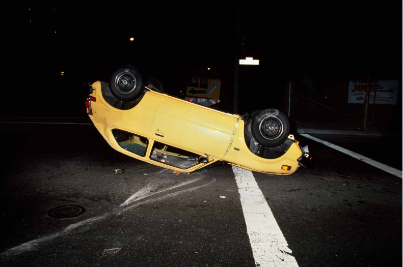 Upside down yellow car, 1980 I remember seeing this accident in the middle of the night and just knowing I'd missed what happened by only seconds. Parts of the car were still making noise. Oddly no one was around so I took this photo and moved on