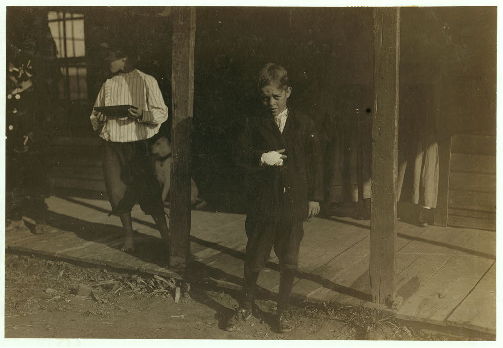 """Lewis hines, Accident to young cotton mill worker. Giles Edmund Newsom (Photo October 23rd, 1912), while working in Sanders Spinning Mill, Bessemer City, N.C., August 21st, 1912, a piece of the machine fell on to his foot mashing his toe. This caused him to fall on to a spinning machine and his hand went into unprotected gearing, crushing and tearing out two fingers. He told the Attorney he was 11 years old when it happened. His parents are now trying to make him 13 years old. The school census taken at the time of the accident makes him12 years (parents' statement) and school records say the same. His school teacher thinks that he is 12. His brother (photo 3071) is not yet 11 years old. Both of the boys worked in the mill several months before the accident. His father, (R.L. Newsom) tried to compromise with the Company when he found the boy would receive money and not the parents. The mother tried to blame the boys for getting jobs on their own hook, but she let them work several months. The aunt said """"Now he's jes got to where he could be of some help to his ma an' then this happens and he can't never work no more like he oughter.""""]. Location: [Bessemer, North Carolina]."""