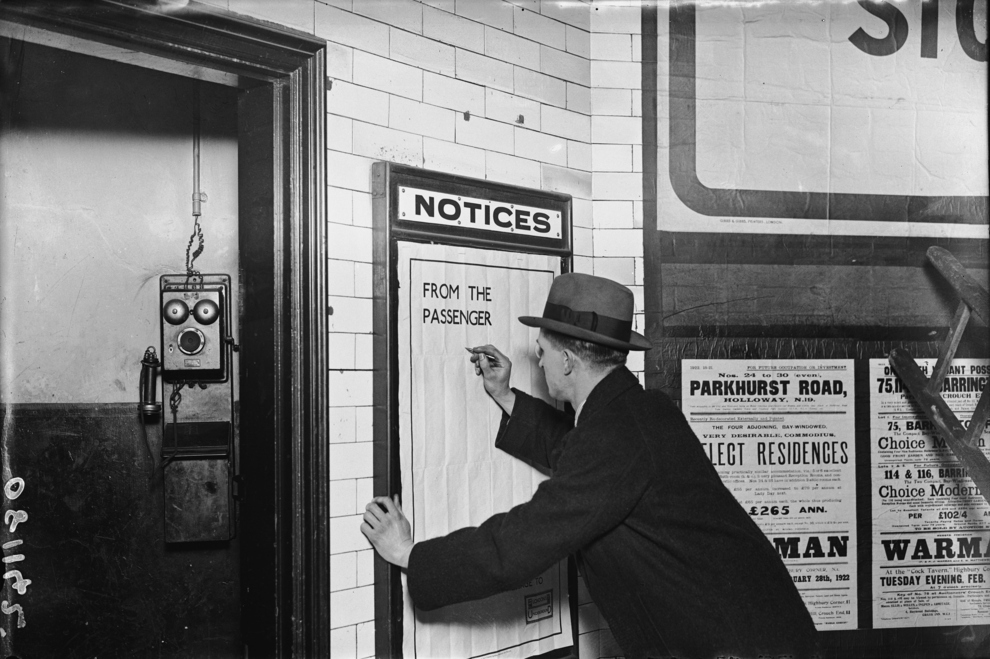 A man writing on a complaints poster, 1922.