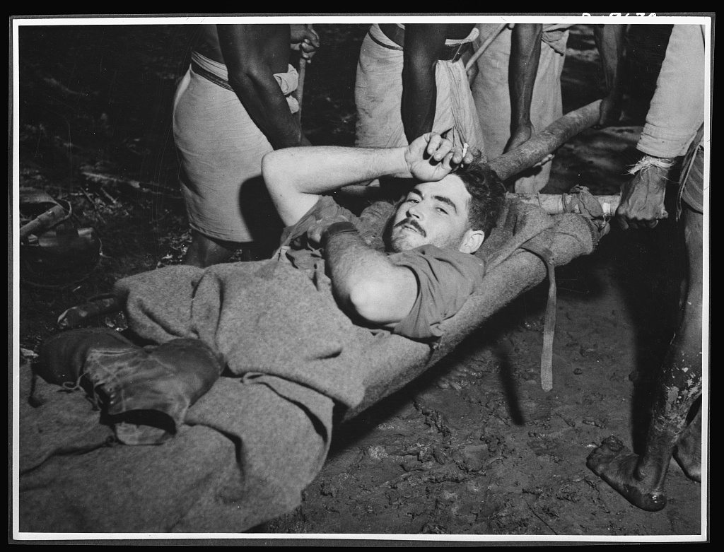 Natives aid Allied drive in New Guinea jungles. Corporal R.D. Somerville being taken from a dressing station in New Guinea just after the fighting at Oive. Without the native carrier service, Allied casualties would have been greater in this area