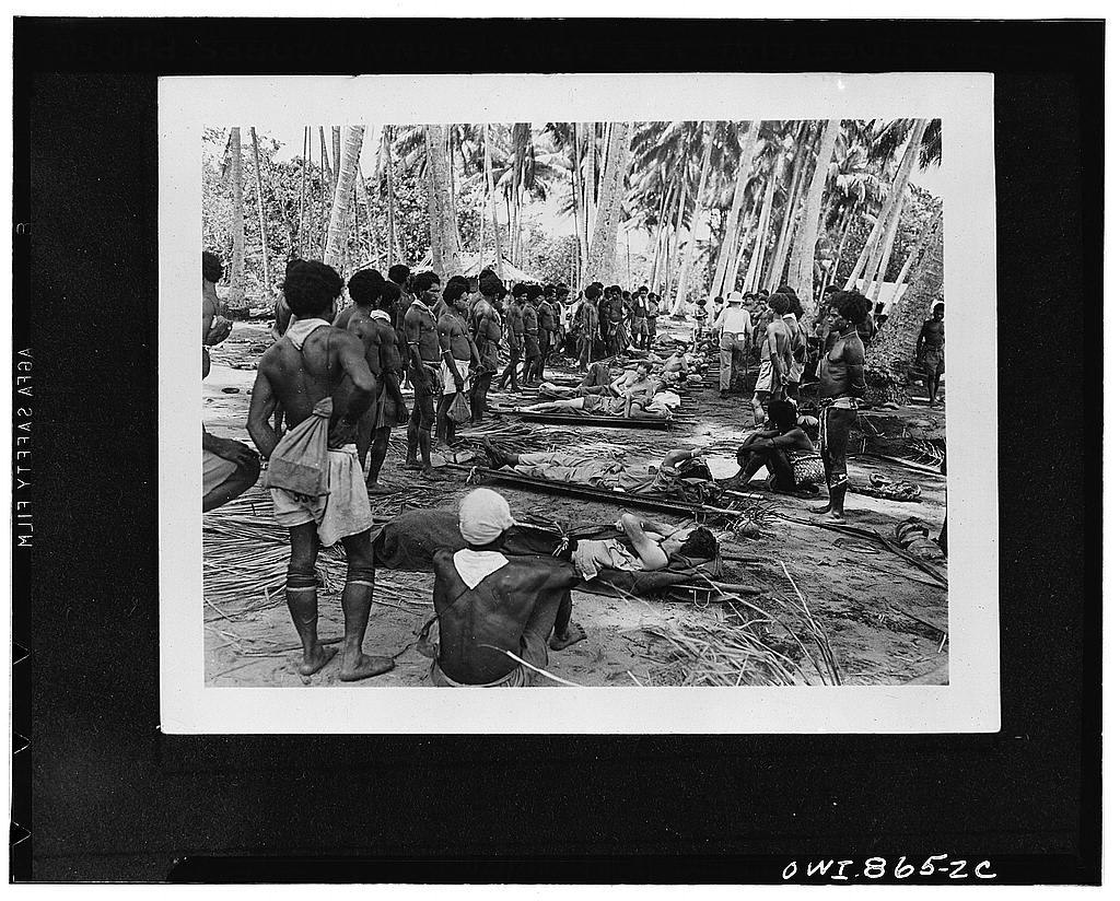 1942. Buna (vicinity), New Guinea. Native stretcher bearers in New Guinea carrying American wounded from the front lines pause to rest themselves and the soldiers in the shade of a coconut grove, enroute to hospitals in the rear