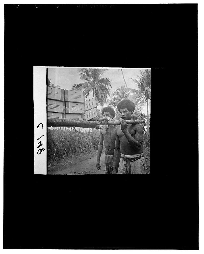 Buna, New Guinea. Papuan natives shouldering litters carrying blood plasma to the evacuation stations just behind the front liine at Buna. They are given a large measure of credit for the Allied successes in New Guinea. The litters are made of betelwood, by hand, and bound with bark rope
