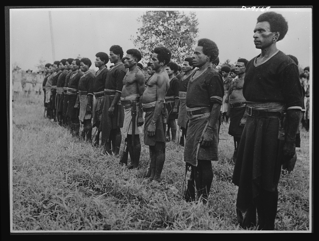 Natives aid Allied drive in New Guinea jungles. Natives who played a great part in the Allied success in New Guinea are addressed by General Vasey. Native police form a guard of honor as native carriers are presented with medals