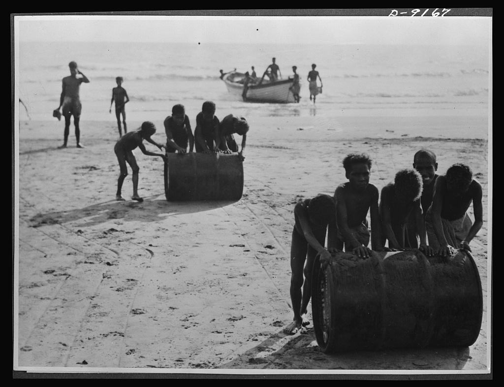 Natives aid Allied drive in New Guinea jungles. Even the native youngsters assist the Allied troops in the New Guinea offensive. Boys are shown helping to unload petrol at a beach in this area