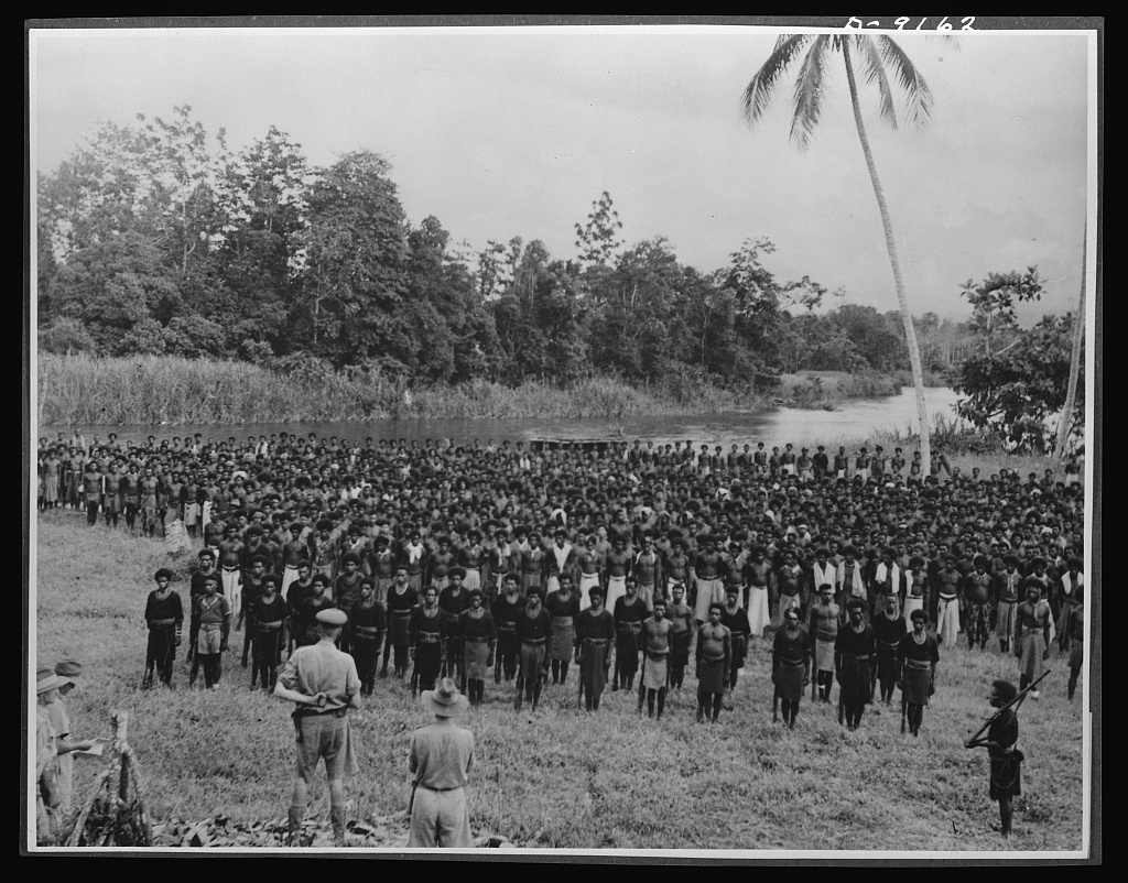Natives aid Allied drive in New Guinea jungles. The Australian Commonwealth has decorated hundreds of New Guinea natives for their invaluable services to the Allied cause. General Vassey is shown at a ceremony at which medals were presented to a large group of stretcher and supply carriers