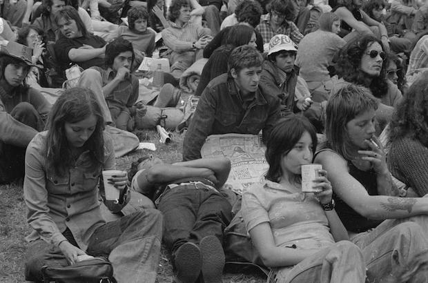 23rd August 1974: A young audience sitting on the grass at the Reading Music Festival.