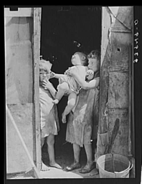 "Children of Mays Avenue camp dressed in old sacks. Their father is a ""trasher."" Oklahoma City, Oklahoma 1 negative : safety ; 3 1/4 x 4 1/4 inches or smaller. Contributor: Lee, Russell Date: 1939"