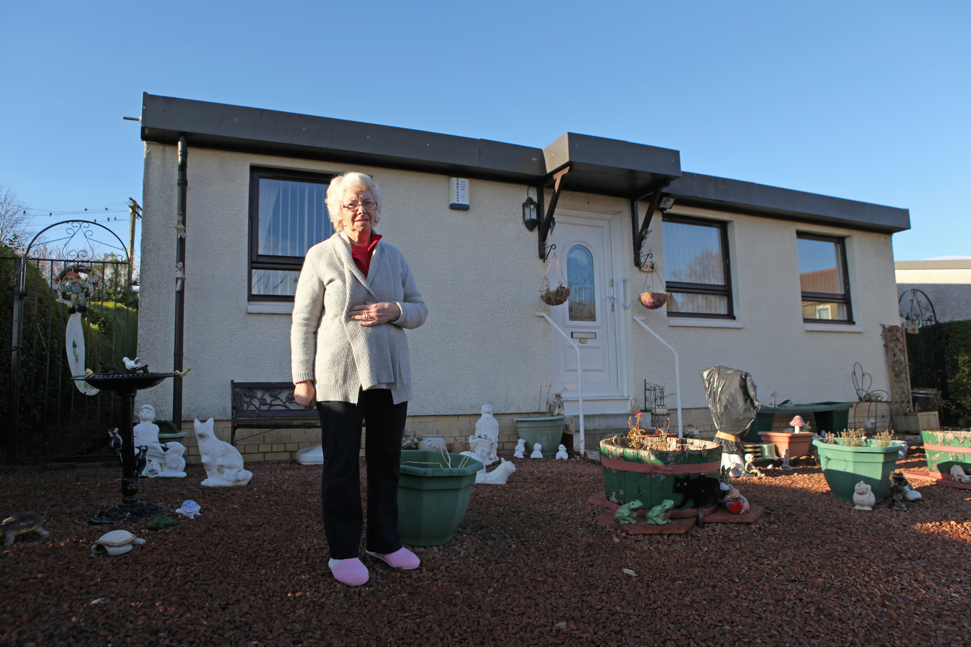 A lady outside her AIROH prefab, 2012. Post-war prefabricated houses in Paisley, near Glasgow, Scotland