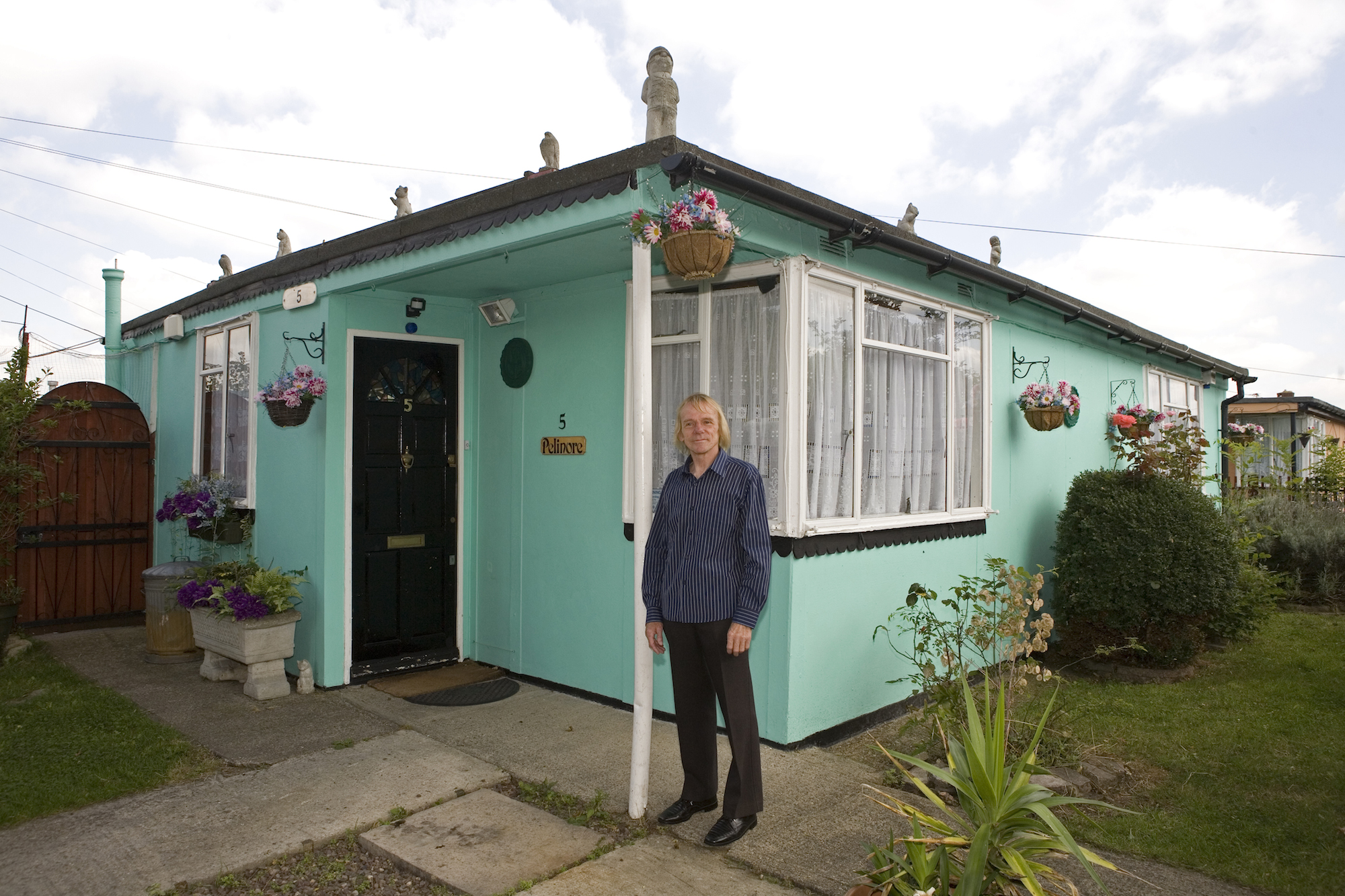 Jim Blackender in front of his prefab in 2009. Jim fought and lost. He raised an army of residents to save the prefabs from demolition but the battle ended up in a ballot which led by 54% to 46% to the 'regeneration' of the estate. By regeneration, the council means demolition of the post-war bungalows and replacement with double and triple storeys dwellings. The idea is to triple the density of the population but it's difficult to find out more as Lewisham is remaining very discreet about the future. The demolition process should have started in October 2012 but in June 2013, it still hadn't begun. On the estate, more and more prefabs are being boarded up. Residents were hoping they would be rehoused in new houses at the same location but it doesn't look like it will happen, so they are ending up accepting other housing options offered by the council as Jim and his wife Lauren did. In September 2012, they left their prefab for good for a 2 bedroom attached house in Rochester, Kent. I paid them a visit in Winter 2013. They both became very emotional when talking about their prefab. The scar hasn't healed yet. 'In a prefab, youíve got a two-bedroom detached property and unless you have lots of money, youíre never ever going to get that again. It was something we were fortunate to have as council tenants. Once the prefabs are gone, theyíre gone forever; youíre never going to get back to a place like that. I liked everything about the prefab ñ I couldn't put a finger on it. It was the people, the location. When we moved in 20-odd years ago, there was a really strong community, and there was no way anyone could have taken that place from the residents. But itís been left to rot, the Council should have been carrying out repairs, painting and redecorating, so people would want to live there, but hardly anything has been done to the estate. Itís depressing to watch it fall into disrepair'.