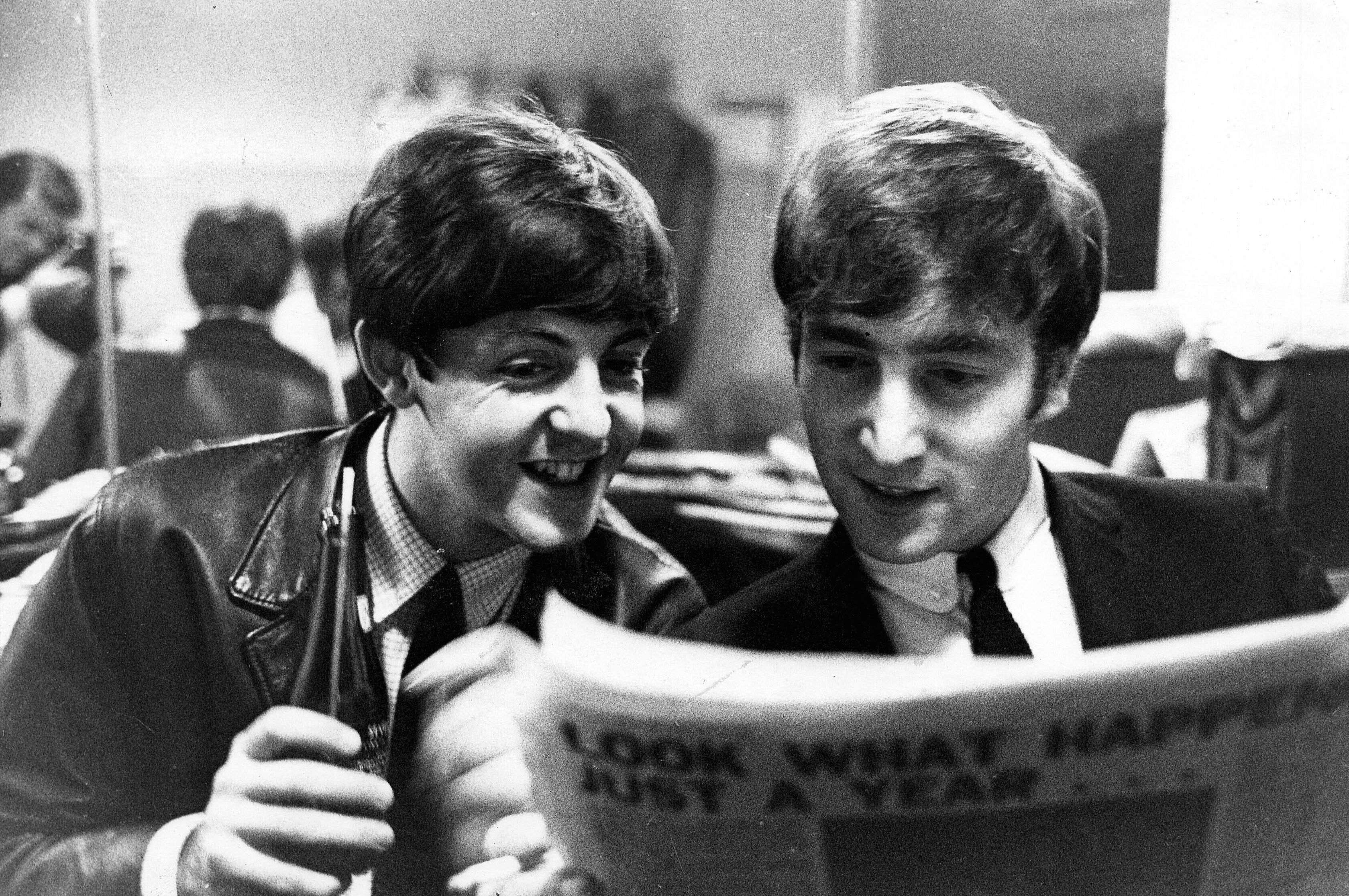 PAUL MCCARTNEY AND JOHN LENNON READING NEWSPAPER