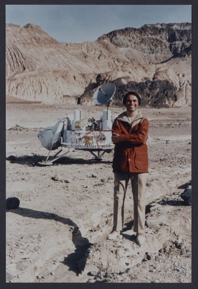 Sagan with Viking lander model. Photographed by Bill Ray, Death Valley, 1980.
