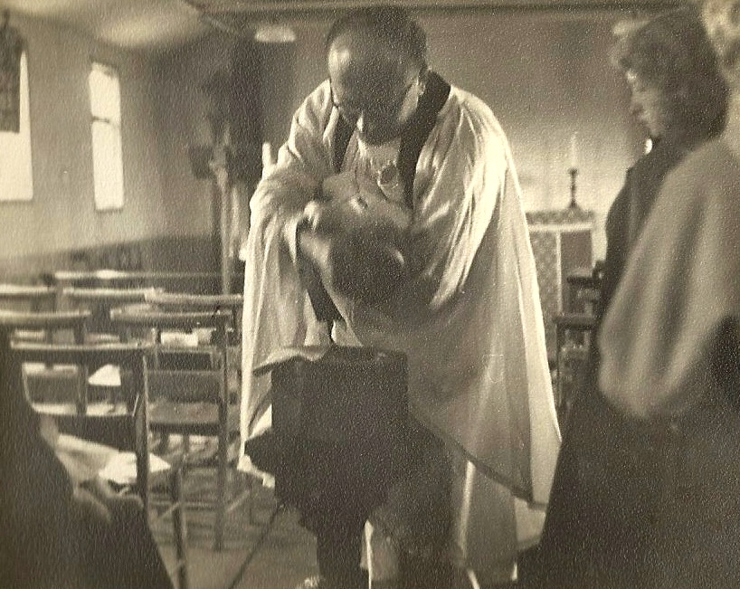 A child being baptised at St Marks Church by a priest, a woman is watching