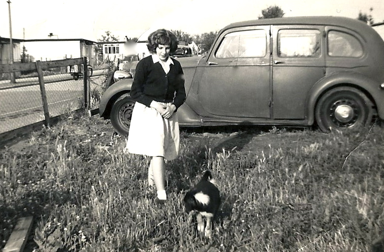 Woman in a prefab (uni-seco) garden with hen. A car is parked in the prefab garden. There is a row of uni-seco prefabs in the background.