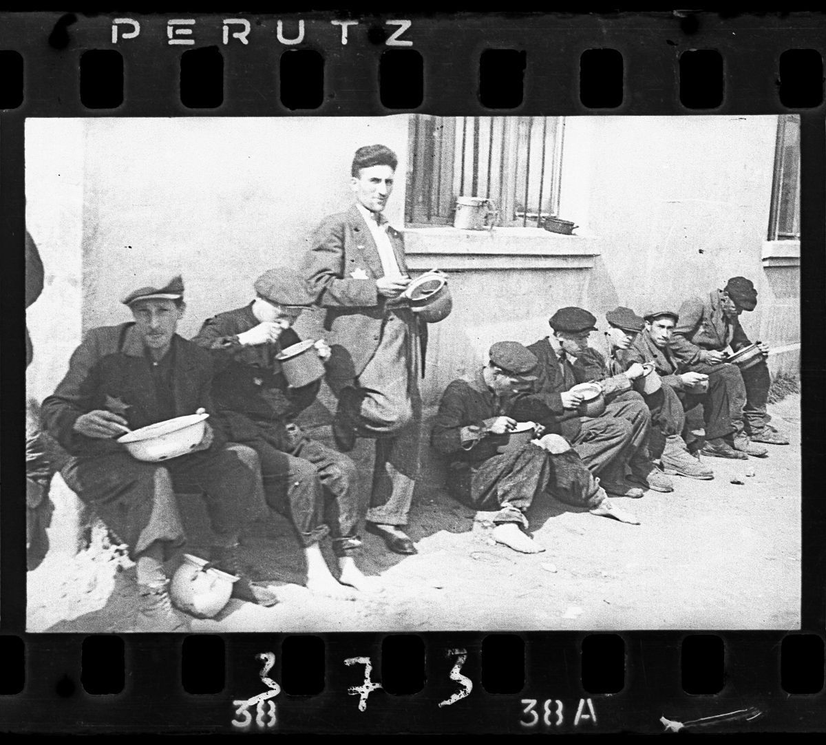 """c. 1940-1944 """"Soup for lunch"""" (Group of men alongside building eating from pails)."""