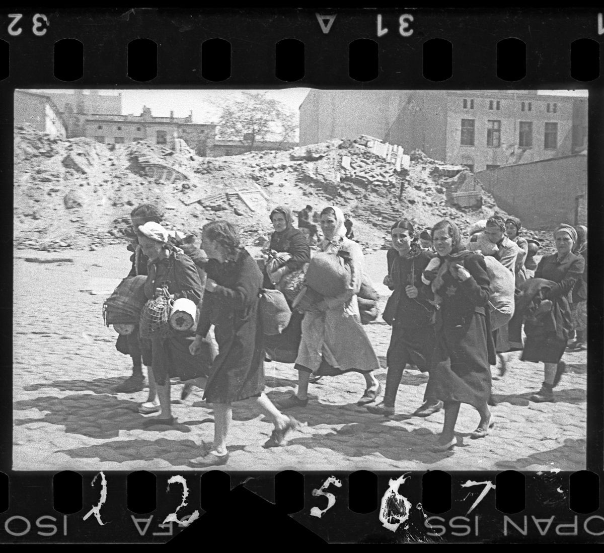 c. 1940-1944 A group of women with sacks and pails, walking past synagogue ruins heading for deportation.