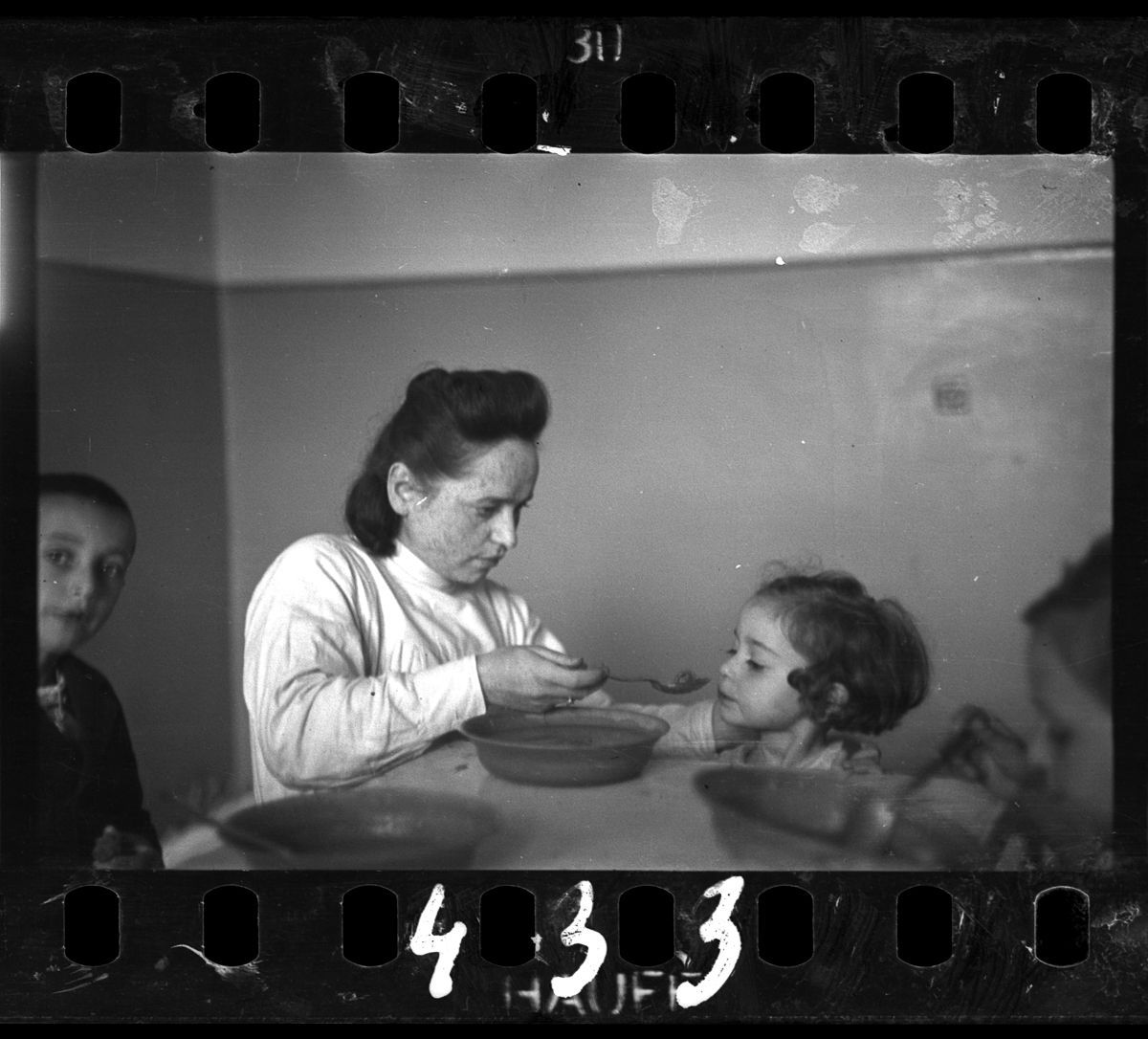 c. 1940-1944 A nurse feeding children in an orphanage.