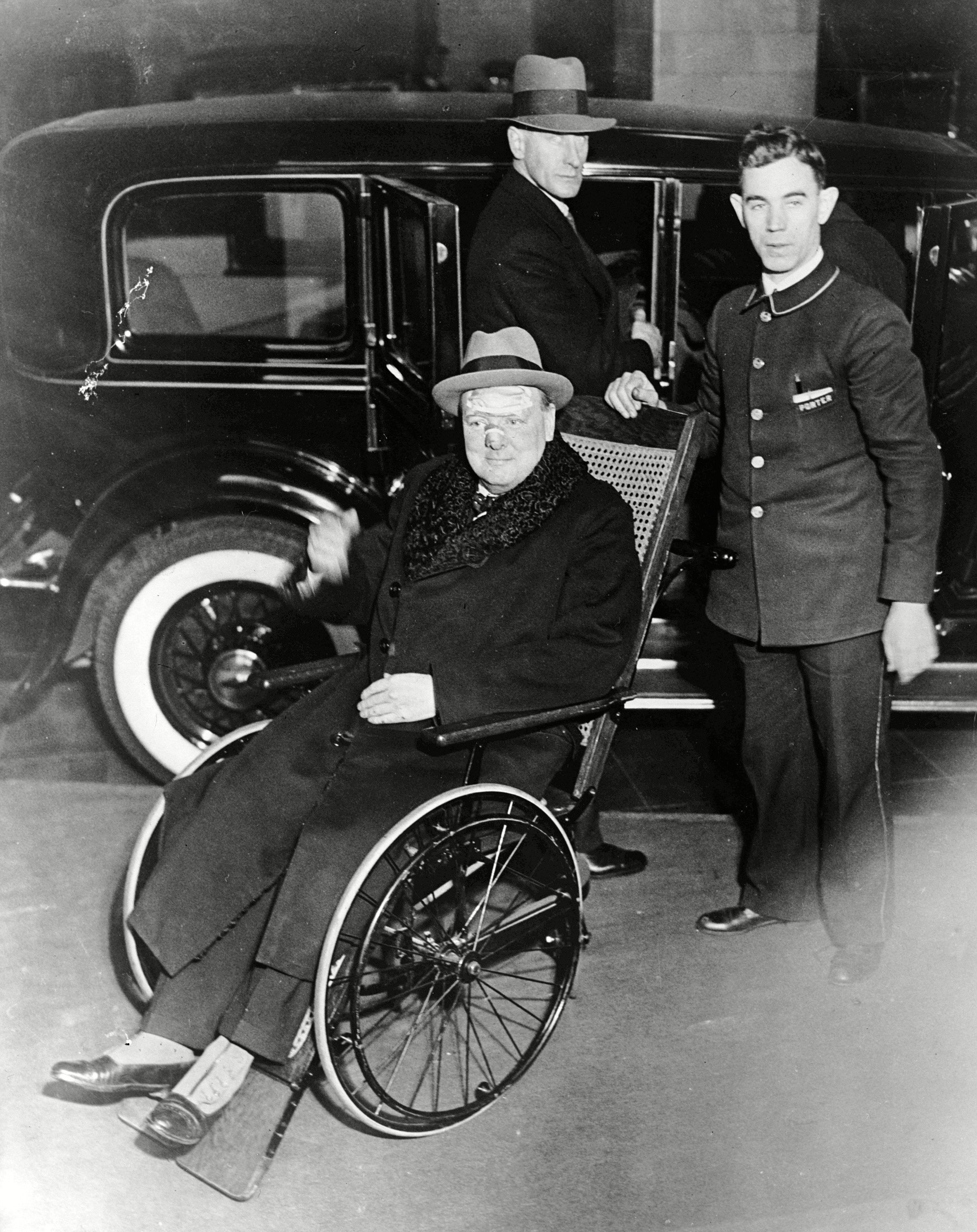 Winston Churchill leaves the Lenox Hill hospital, New York, in a bath chair with bandages on his face. Churchill is recovering from an accident in which he was knocked down by a taxi driver in Fifth Avenue November 3 1931