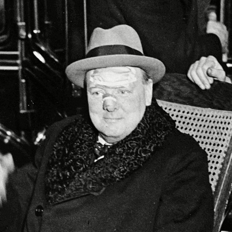 Winston Churchill leaves the Lenox Hill hospital, New York, in a bath chair with bandages on his face. Churchill is recovering from an accident in which he was knocked down by a taxi driver in Fifth Avenue