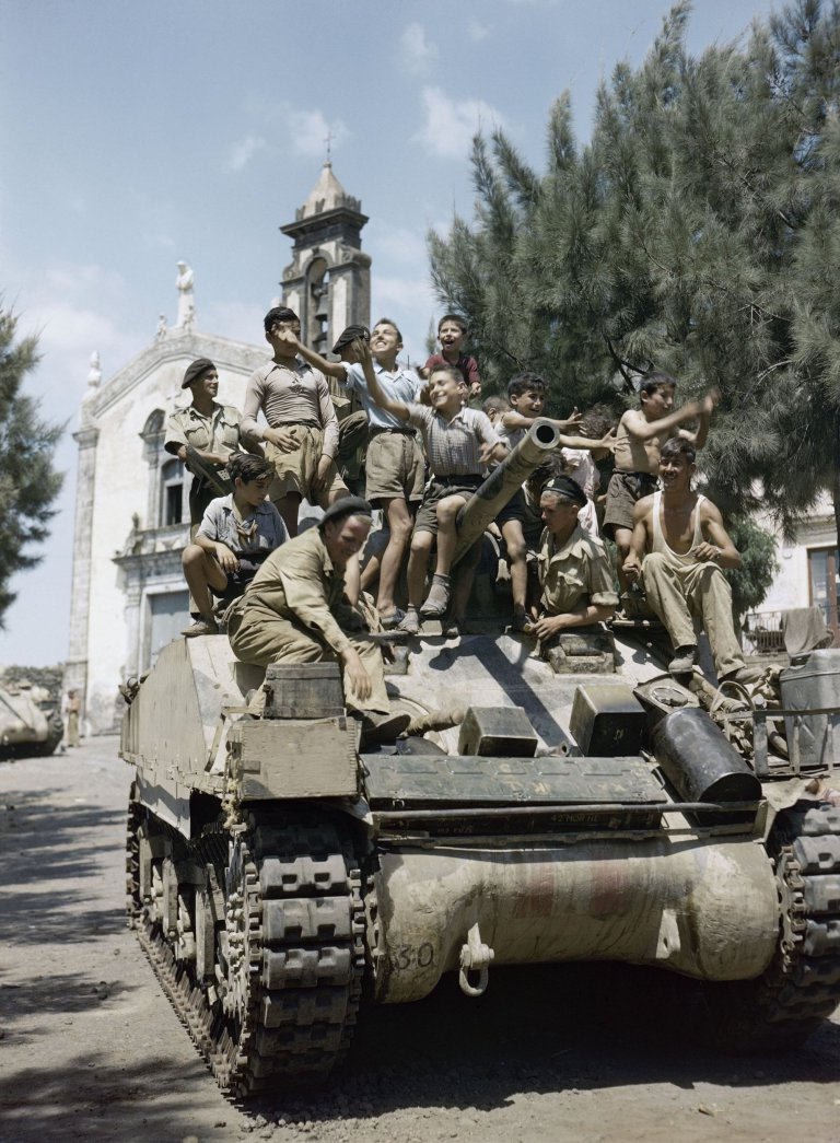 Local children crowding aboard a Sherman tank of the 3rd County of London Yeomanry in Sicily, August 1943